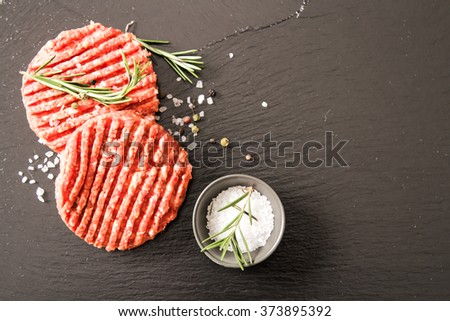 Raw Ground beef meat Burger steak cutlets on a black background stone - stock photo