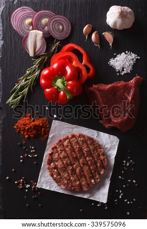 Raw Ground beef meat Burger steak cutlets with ingredients on the board. vertical view from above