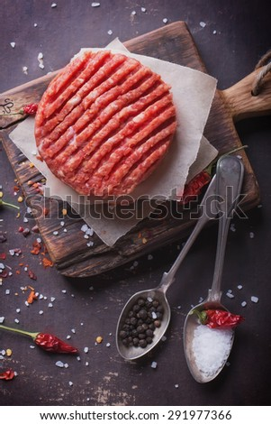 Raw Ground beef meat Burger steak cutlets with seasoning on vintage wooden boards, black background - stock photo