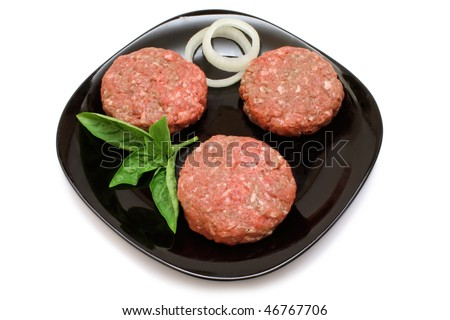 Raw hamburger patties on a black plate with onion rings and Basil garnish, isolated on white with clipping path
