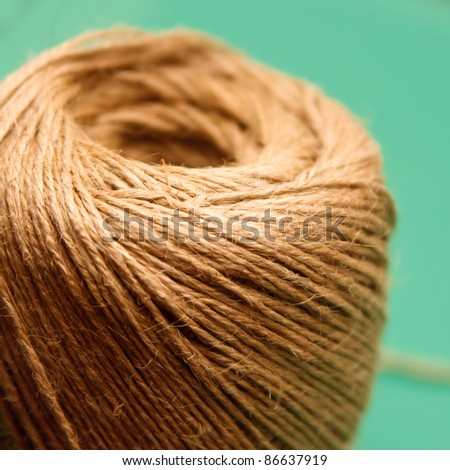 Raw hemp thread role closeup on green background - stock photo