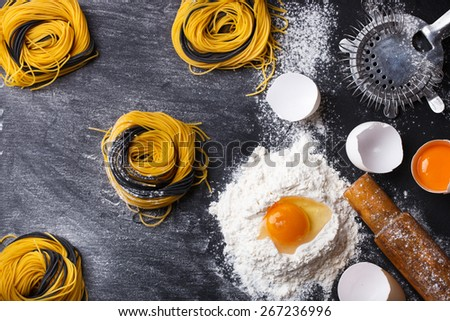 Raw homemade pasta and ingredients on a black background.selective focus - stock photo