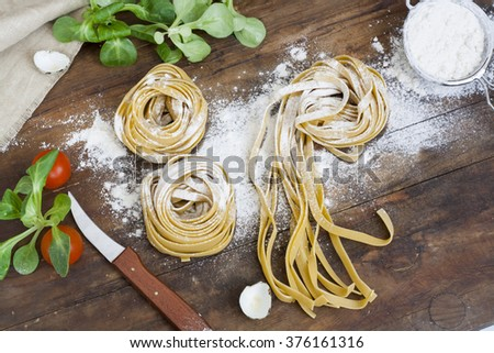 Raw homemade pasta, quail easter eggs in a aluminum cup, green lettuce, tomatoes and flour on wooden table - stock photo
