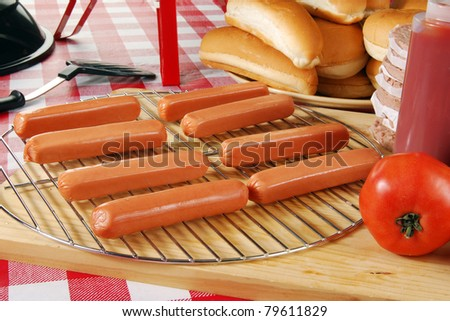 Raw hot dogs on the grill ready to be barbecued