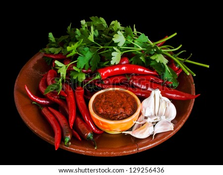 Raw hot sauce adjika and ingredients over black background - stock photo
