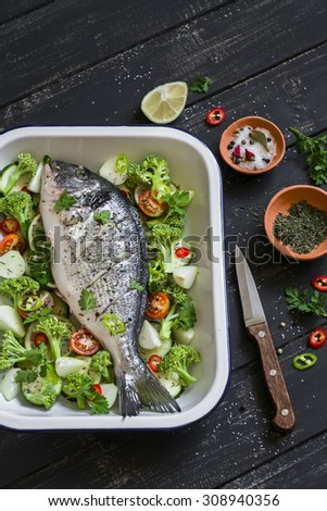 raw ingredients - Dorado fish and vegetables - broccoli, zucchini, onions, peppers, lime and spices on a dark wooden surface, cooking baked fish with vegetables - stock photo