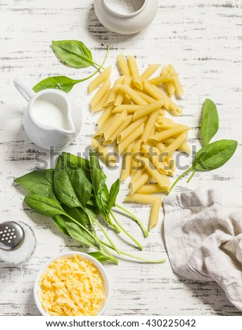 Raw ingredients for making pasta with spinach cream sauce - penne pasta, fresh spinach, cream, cheese and spices on a light wooden background - stock photo