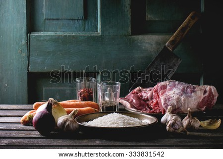Raw ingredients for pilaf lamb, rice, carrots, onion, garlic and spices with meat backsword over wooden table. Dark rustic style. - stock photo
