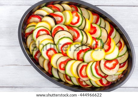 Raw ingredients for traditional French casserole, ratatouille: slices of zucchini, red bell pepper, yellow squash, eggplant in a baking dish, view from above - stock photo