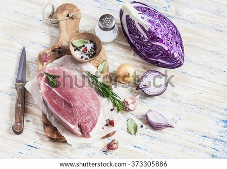 Raw ingredients - meat, red cabbage, onion, garlic, spices and herbs. Cooking delicious and healthy lunch. On light  wooden rustic background - stock photo