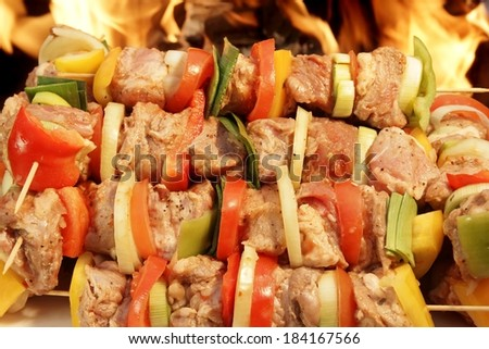 Raw Kebabs in a heap before BBQ Grill and flames in background. - stock photo