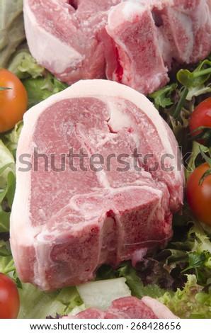 raw lamb chops with cherry tomato on fresh salad - stock photo