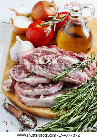 Raw lamb cutlets with vegetables, herbs and spices on wooden chopping board - stock photo