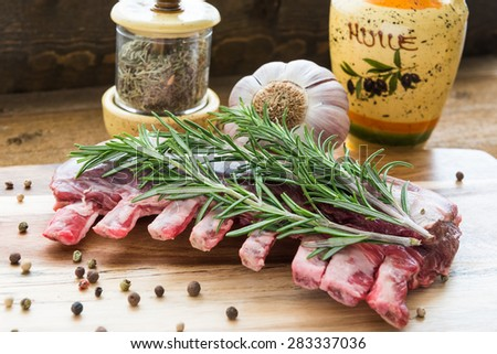 Raw lamb ribs with rosemary, pepper, garlic and oil on wooden board. Front view. - stock photo