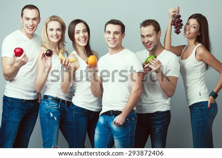 Raw, living food, veggie concept. Group portrait of healthy boys, girls in white t-shirts, sleeveless shirts and blue jeans standing with fruits, posing over gray background. Urban style. Studio shot