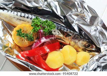 Raw mackerel and vegetables on tinfoil  - stock photo