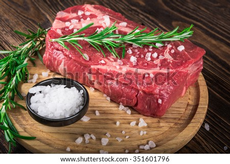 Raw marbled meat steak Ribeye on dark wooden background - stock photo