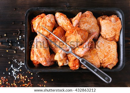 Raw Marinated chicken meat wings and legs for BBQ, served in plastic box with seasoning and vintage meat fork over dark wooden background. Top view - stock photo