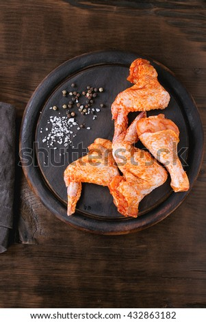 Raw Marinated chicken meat wings and legs for BBQ, served on round wood chopping board with seasoning over dark wooden background. Top view with copy space. - stock photo
