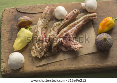 raw marinated lamb cutlets on wooden board - stock photo