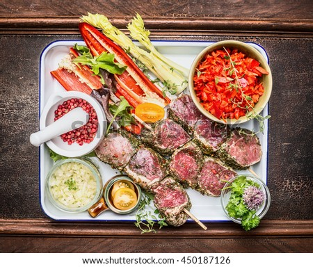 Raw marinated meat skewers with spices and vegetables for grill or roasting on dark wooden background, top view