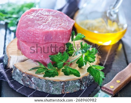 raw meat and parsley on the table - stock photo