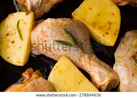 Raw meat and potatoes with spices on the pan - stock photo