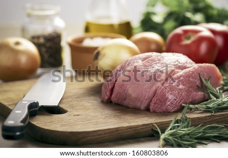 Raw meat and vegetables on cutting board - stock photo