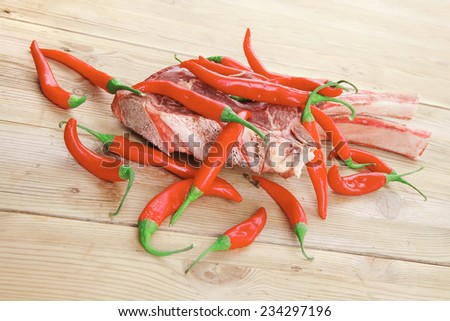 raw meat : boned fresh lamb ribs served with red chili pepper on wooden table - stock photo