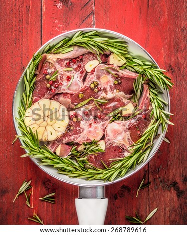 Raw meat Double lamb loin chops with rosemary and garlic in white frying pan on red wooden background, top view - stock photo