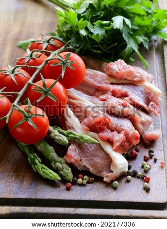 raw meat, lamb chops with vegetables on wooden board - stock photo