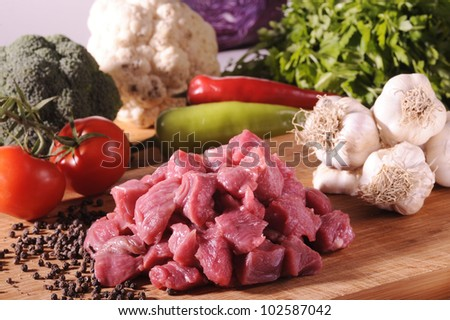 Raw Meat on chopping board with vegetables - stock photo