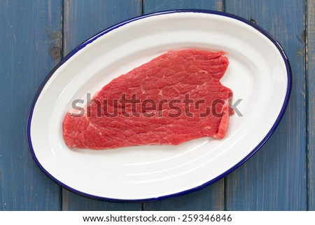 raw meat on white dish on blue background - stock photo