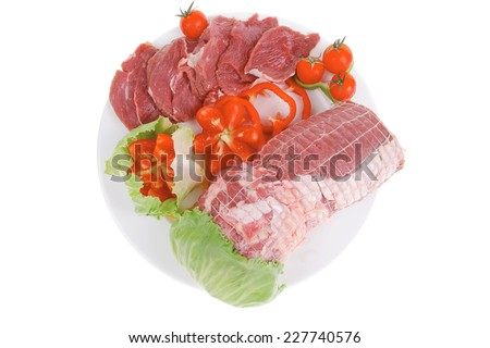 raw meat on white plate with vegetables - stock photo