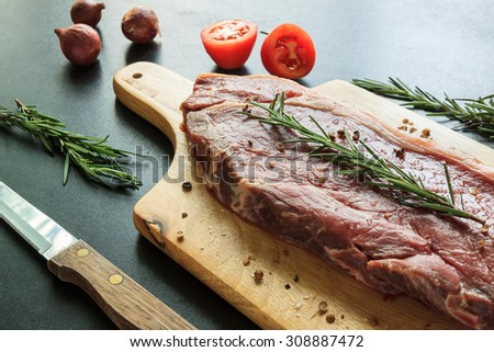 Raw meat on wood cutting board with knife tomato and rosemary - stock photo