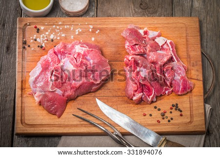 Raw meat  on wooden cutting board with knife, spices and olive oil - stock photo
