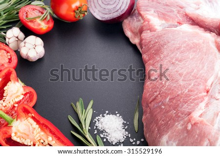 Raw meat pork with spices and vegetables on a dark background. Ingredients for cooking. Selective focus - stock photo