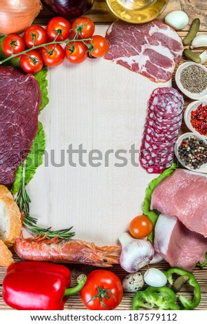 Raw meat, sausage, vegetables and spices on wooden table with place for your text - stock photo