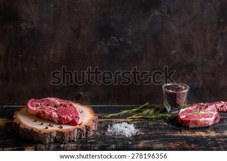 Raw meat steak on dark wooden background ready to roasting - stock photo