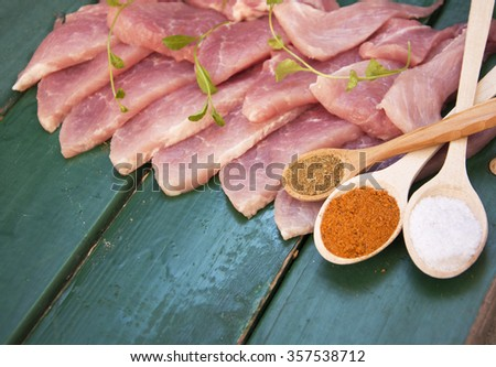 Raw meat steak on dark wooden board. salt and spices on wooden spoons, Thin slices of pork. selective focus - stock photo