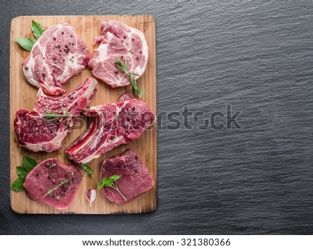 Raw meat steaks with spices on the cutting board. - stock photo