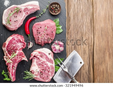 Raw meat steaks with spices on the wooden cutting board. - stock photo