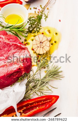 Raw meat with herbs,spices and oil on white wooden background, place for text - stock photo