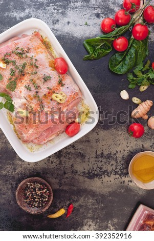 Raw meat  with spices ready for roasting. Fresh raw meat with cooking ingredients on rustic background. Top view, vintage toned image, blank space - stock photo