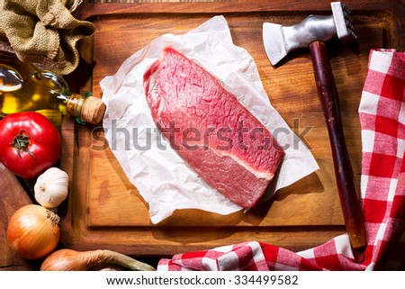 raw meat with vegetables on wooden board - stock photo