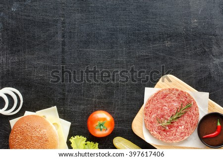 Raw minced beef (patty) with herbs, sesame bun, cheese, tomato, lettuce, onion, pickle, hot BBQ sauce, chili. Homemade hamburger ingredients. Black background. Space for text. - stock photo