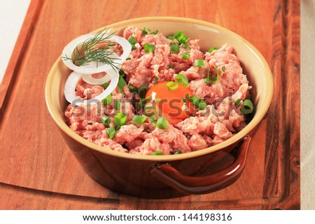 Raw minced meat and egg yolk in a ceramic pot - stock photo