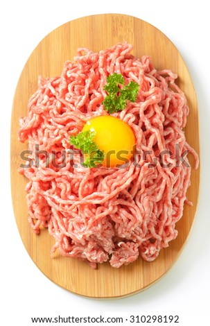 raw minced meat with egg yolk on oval wooden cutting board - stock photo