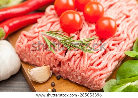 raw minced meat with vegetables on wooden board, selective focus