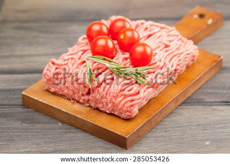 raw minced meat with vegetables on wooden board, selective focus - stock photo